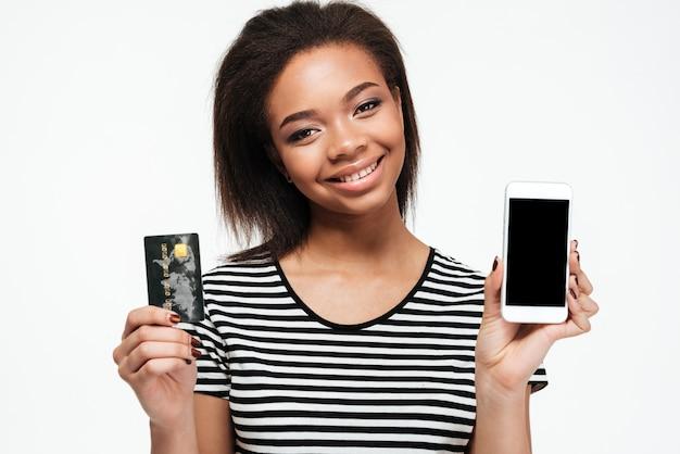 Szczęśliwa młoda afrykańska dama używa telefon i trzymający kartę debetową.