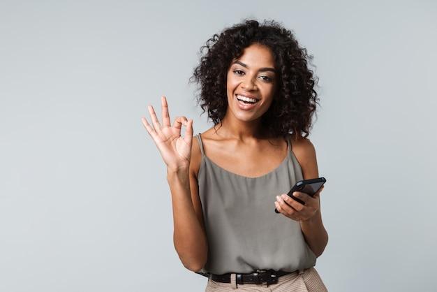 Szczęśliwa młoda afrykańska kobieta niedbale ubrana stojąca na białym tle, trzymając telefon komórkowy, ok