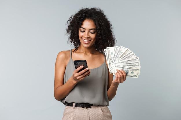 Szczęśliwa młoda afrykańska kobieta stojąca na białym tle, trzymając kilka banknotów pieniędzy, przy użyciu telefonu komórkowego