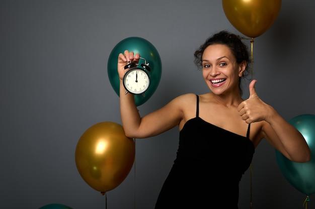 Szczęśliwa młoda afrykańska kobieta trzyma budzik, jest północ, pokazując kciuk do góry, uśmiechając się patrząc na kamery, na białym tle na szarym tle z balonami. nowy rok, koncepcja wesołych świąt dla reklamy