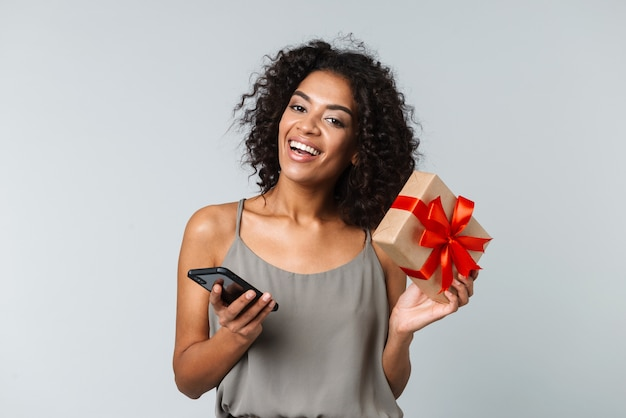 Szczęśliwa młoda afrykańska kobieta ubrana niedbale stojąc na białym tle, przy użyciu telefonu komórkowego, pokazując pudełko