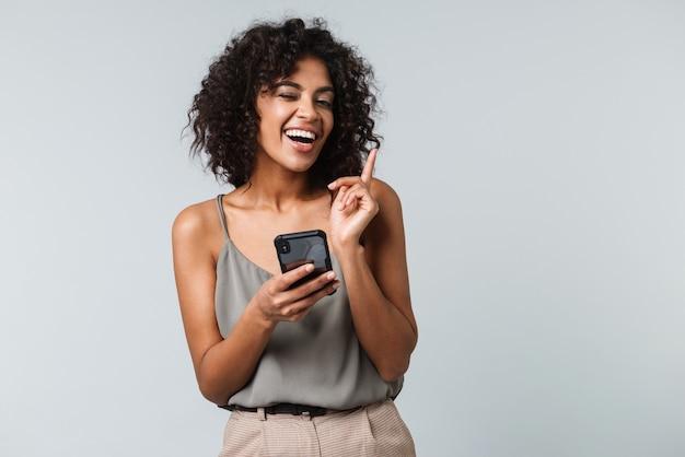 Szczęśliwa młoda afrykańska kobieta ubrana niedbale stojąc na białym tle, przy użyciu telefonu komórkowego