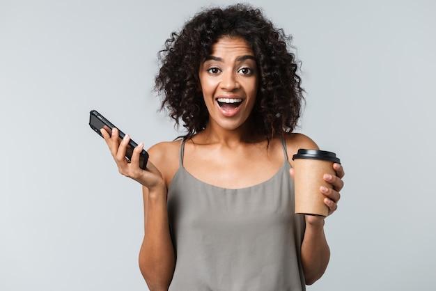 Szczęśliwa młoda afrykańska kobieta ubrana niedbale stojąc na białym tle, rozmawiając przez telefon komórkowy, trzymając filiżankę kawy na wynos