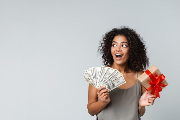 Szczęśliwa młoda afrykańska kobieta ubrana niedbale stojąc na białym tle, trzymając pudełko, pokazując banknoty