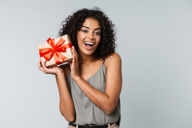Szczęśliwa młoda afrykańska kobieta ubrana niedbale stojąc na białym tle, trzymając pudełko