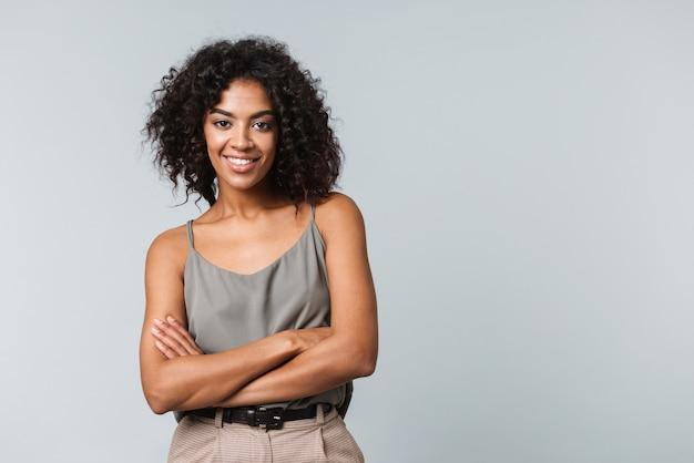 Szczęśliwa młoda afrykańska kobieta ubrana niedbale stojąc na białym tle z założonymi rękoma