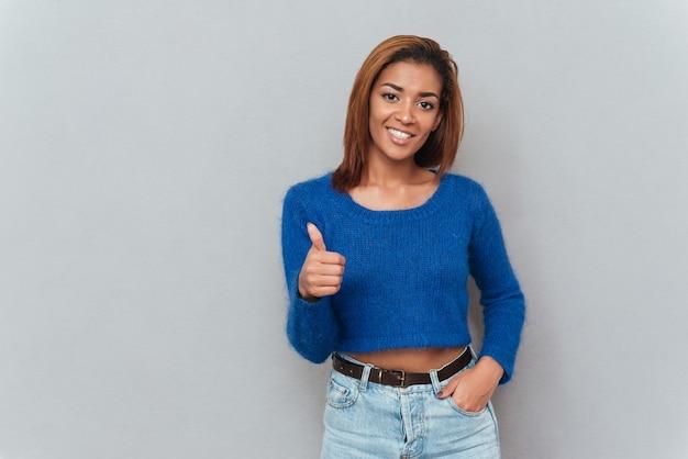 Szczęśliwa Młoda Afrykańska Kobieta W Swetrze Pokazując Kciuk Do Góry I Drugiej Ręki Trzymającej W Kieszeni. Premium Zdjęcia