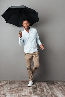Szczęśliwa młoda afrykańska mężczyzna pozycja z otwartym parasolem