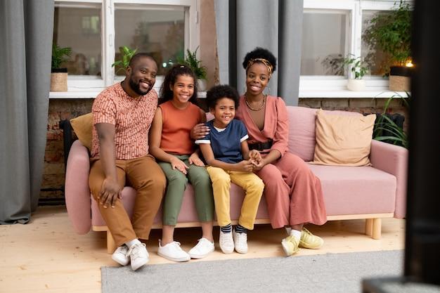 Szczęśliwa młoda afrykańska rodzina ojca, matki, syna i córki siedzi na kanapie przy oknie w salonie i ogląda program telewizyjny lub film