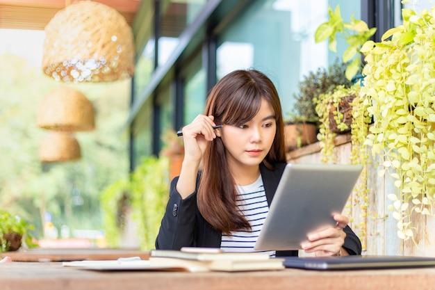 Szczęśliwa młoda atrakcyjna biznesowa kobieta w swobodnym garniturze pracująca na swoim komputerze na patio na świeżym powietrzu