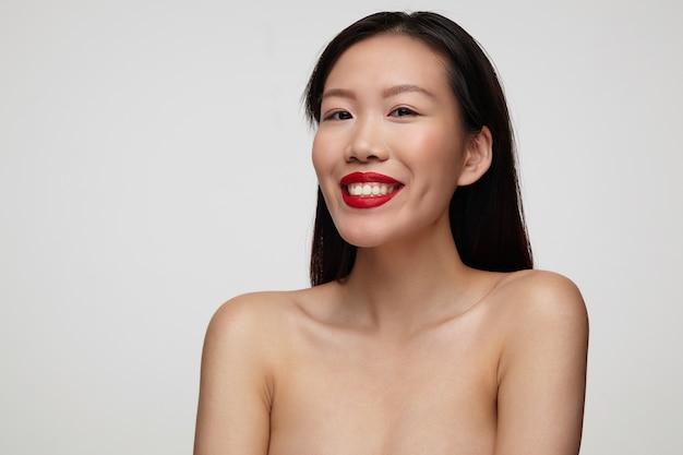 Szczęśliwa młoda atrakcyjna brązowooka brunetka dama z czerwonymi ustami wyglądająca wesoło i uśmiechnięta szeroko, stojąca nad białą ścianą z rękami w dół