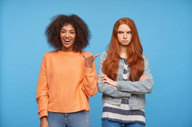 Szczęśliwa młoda atrakcyjna brązowowłosa ciemnoskóra kobieta wskazuje kciukiem na swojego surowego młodego dość długowłosego przyjaciela, stojąc nad niebieską ścianą
