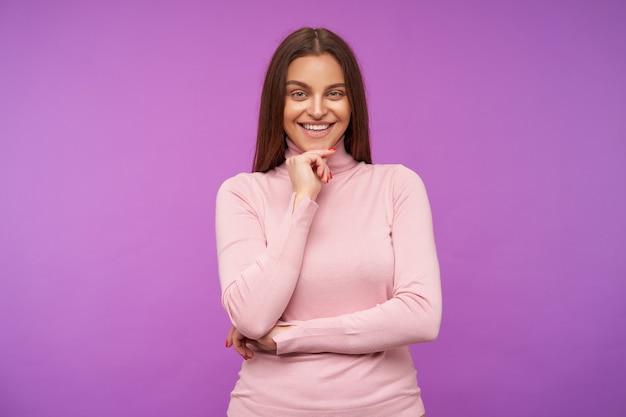 Szczęśliwa młoda atrakcyjna brązowowłosa kobieta z naturalnym makijażem, trzymając brodę z uniesioną ręką, patrząc wesoło z przodu, odizolowana na fioletowej ścianie