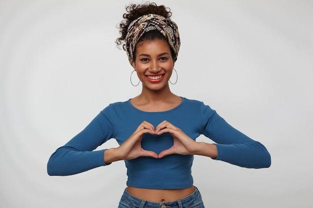 Szczęśliwa młoda atrakcyjna brunetka ciemnoskóra kobieta pokazuje znak miłości z uniesionymi rękami i uśmiecha się radośnie do kamery, stojąc na białym tle