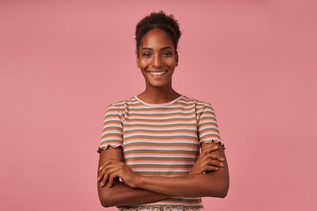 Szczęśliwa młoda atrakcyjna brunettened kobieta z przypadkową fryzurą, trzymając ręce złożone, pozując na różowej ścianie, będąc w miłym nastroju i szeroko uśmiechając się