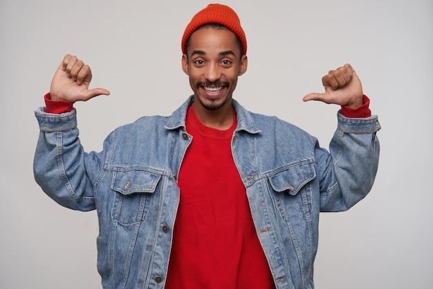 Szczęśliwa młoda atrakcyjna ciemnoskóra brodata brunetka facet pokazuje radośnie na sobie kciukami, uśmiechając się szeroko podczas pozowania na białej ścianie