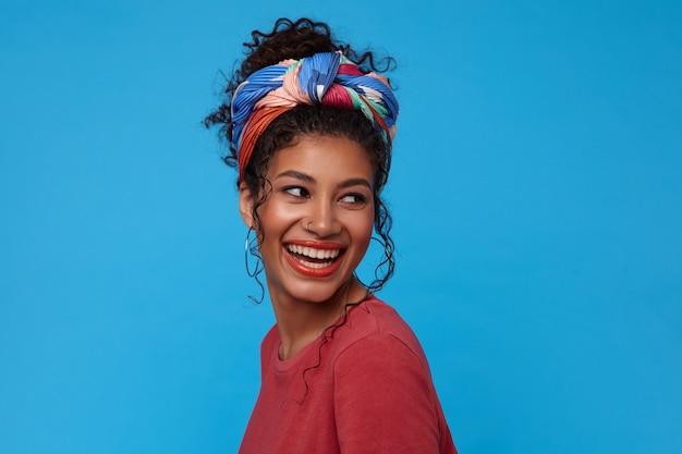 Szczęśliwa młoda atrakcyjna ciemnowłosa kobieta z zebranymi włosami, śmiejąc się radośnie, patrząc radośnie przez ramię, odizolowane na niebieskiej ścianie
