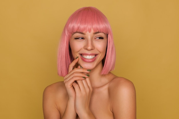 Szczęśliwa młoda atrakcyjna różowowłosa kobieta z krótką fryzurą delikatnie dotykająca jej twarzy z uniesionymi rękami i uśmiechnięta przyjemnie, patrząc na bok, odizolowana na musztardowym tle