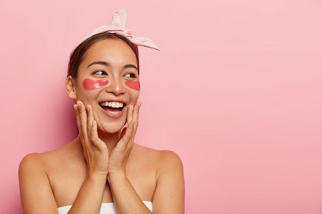 Szczęśliwa młoda azjatka ma maskę kosmetyczną na oczy, pozytywnie się śmieje, delikatnie dotyka twarzy, patrzy na bok, przeprowadza zabiegi kosmetyczne w salonie spa, nosi różową opaskę, stoi owinięta ręcznikiem w pomieszczeniu