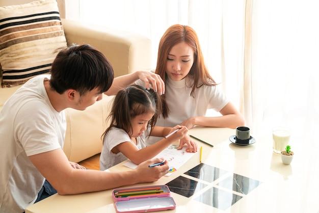 Szczęśliwa młoda azjatka ze swoimi uroczymi rodzicami odrabiając lekcje, ucząc się i spędzając razem czas. azjatycka rodzina, dystans społeczny, nauczanie w domu, praca z domu lub koncepcja miłości