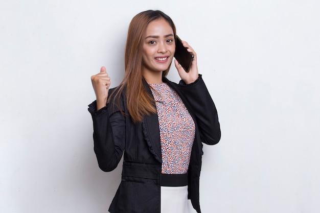 Szczęśliwa młoda azjatycka kobieta biznesu korzystająca z telefonu komórkowego na białym tle