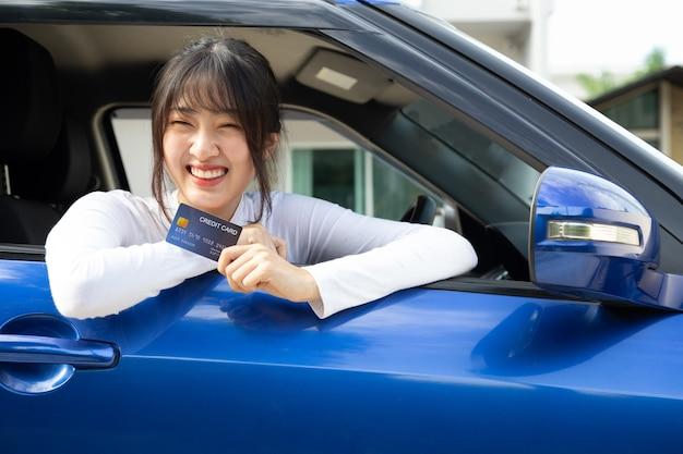 Szczęśliwa młoda azjatycka kobieta kierowca trzyma kartę płatniczą, kartę członkowską, kartę kredytową i siedzi w samochodzie