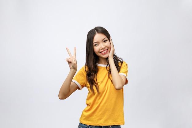 Szczęśliwa młoda azjatycka kobieta pokazuje dwa palce lub gest zwycięstwa