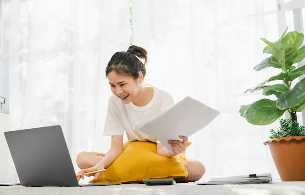 Szczęśliwa młoda azjatycka kobieta pracuje dla laptopu z wykresem dokumentuje od domu na dywanie, spotyka i trenuje online pojęcie.