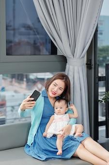 Szczęśliwa młoda azjatycka kobieta siedzi na kanapie i biorąc selfie z córeczką