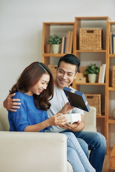 Szczęśliwa młoda azjatycka kobieta siedzi na kanapie w domu i dostaje teraźniejszy od męża
