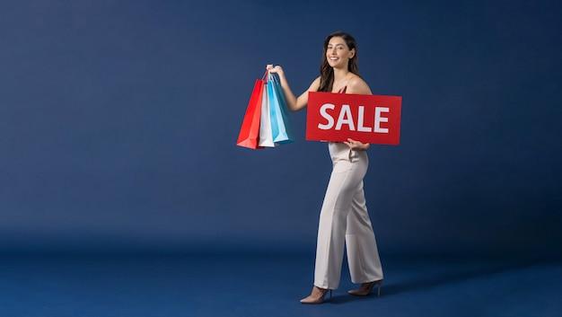 Szczęśliwa młoda azjatycka kobieta trzymająca i prezentująca papierowy baner sprzedaży na zakupy
