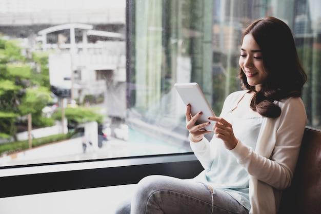 Szczęśliwa młoda azjatycka kobieta używa cyfrową pastylkę i czuciowego szczęście podczas gdy czytający ebook, środki rezerwuje bibliotekę lub naukę na nauczania online online pojęciu