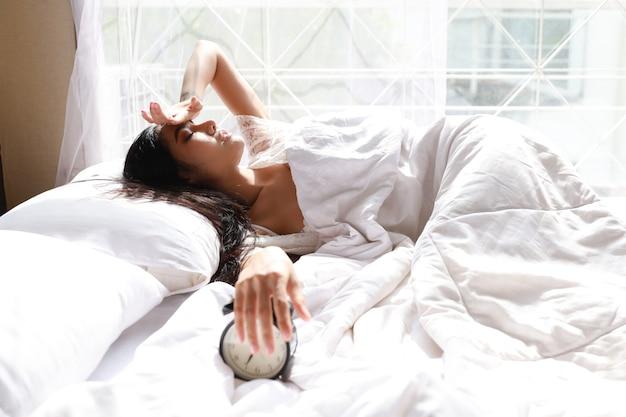 Szczęśliwa młoda azjatycka kobieta w białej bieliźnie, leżąc w łóżku