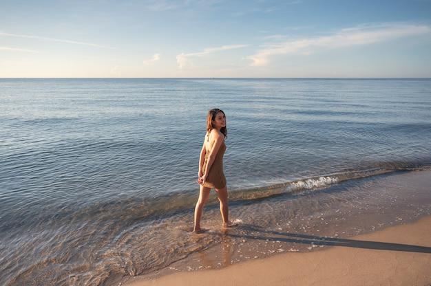 Szczęśliwa młoda azjatycka kobieta w brązowej sukience spacerująca po plaży rano nad tropikalnym morzem na letnie wakacje