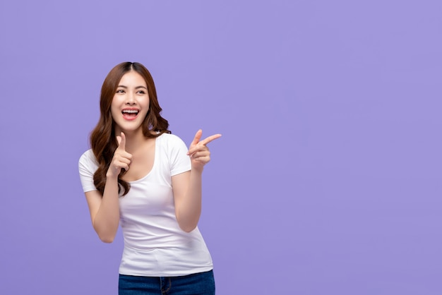 Szczęśliwa młoda azjatycka kobieta wskazuje z oba rękami z dużym uśmiechem