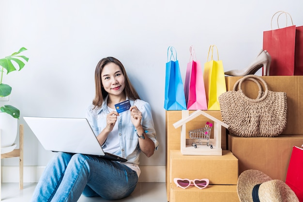 Szczęśliwa młoda azjatycka kobieta z kolorową torbą na zakupy, modnymi przedmiotami i stosem kartonów w domu, przy użyciu karty kredytowej do koncepcji zakupów online