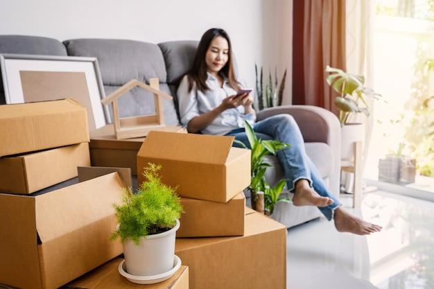 Szczęśliwa młoda azjatycka kobieta za pomocą smartfona w salonie w nowym domu ze stosem pudełek kartonowych na dzień przeprowadzki