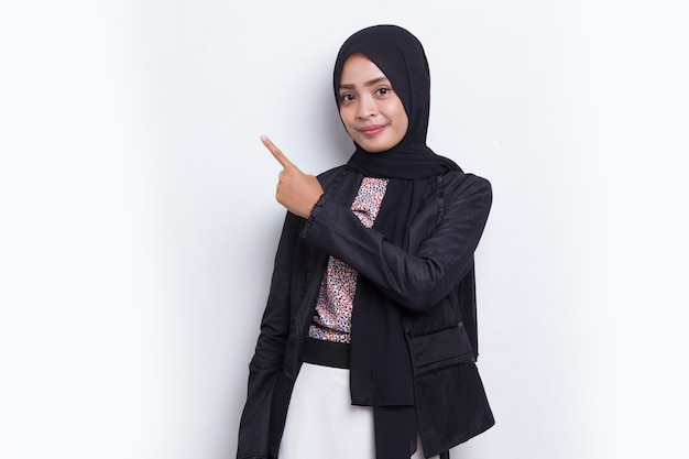 Szczęśliwa młoda azjatycka muzułmańska kobieta wskazująca palcami w różnych kierunkach na białym tle