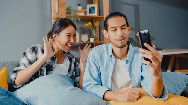 Szczęśliwa młoda azjatycka para mężczyzna i kobieta siedzą na kanapie i rozmawiają z przyjaciółmi i rodziną na smartfonie