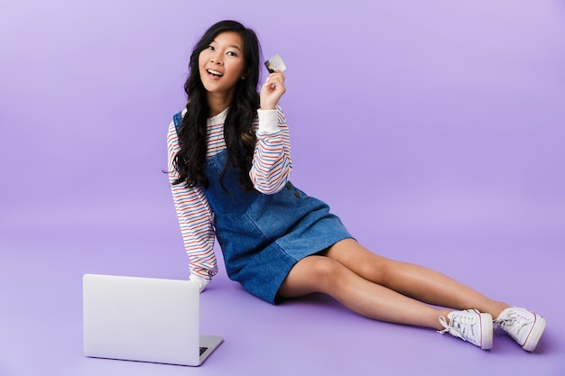 Szczęśliwa młoda azjatycka piękna atrakcyjna kobieta pozowanie na białym tle w pomieszczeniu przy użyciu komputera przenośnego posiadającego kartę kredytową