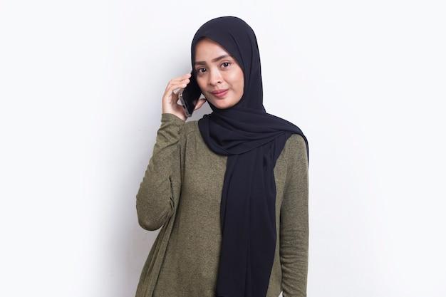 Szczęśliwa młoda azjatycka piękna muzułmańska kobieta korzystająca z telefonu komórkowego na białym tle