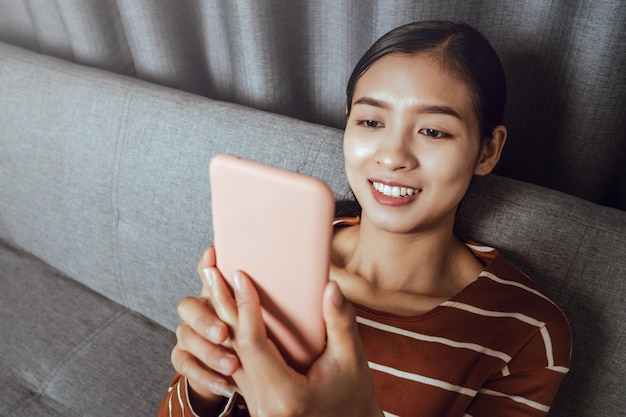 Szczęśliwa młoda azjatycka przyjemna kobieta trzyma smartfon w rękach w domu, uśmiechając się i oglądając śmieszne filmy.