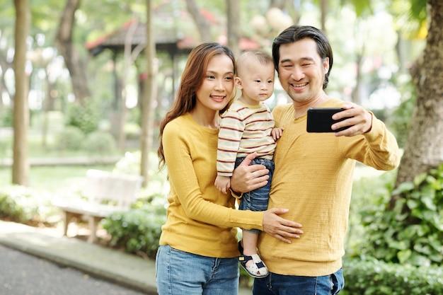 Szczęśliwa młoda azjatycka rodzina trzech razem fotografowanie w parku