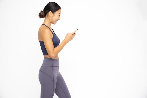 Szczęśliwa młoda azjatycka sportowa kobieta korzystająca z telefonu komórkowego, wpisując wiadomość sms