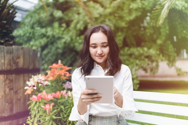 Szczęśliwa młoda azjatycka studentka w parku pracuje na laptopie