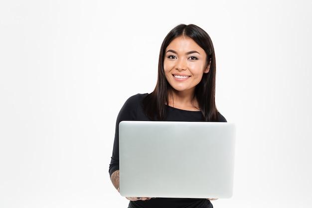 Szczęśliwa młoda azjatykcia dama gawędzi laptopem
