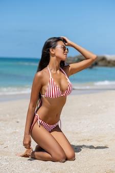 Szczęśliwa młoda azjatykcia kobieta na plaży. plenerowy moda portret dziewczyna cieszy się jej wakacje w gorącej tropikalnej wyspie. seksowne, idealnie dopasowane ciało kobiety.