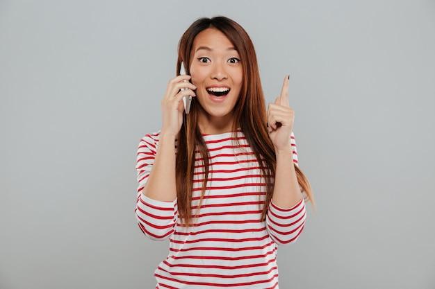 Szczęśliwa młoda azjatykcia kobieta opowiada telefonem ma pomysł.