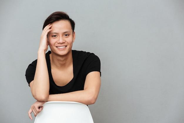 Szczęśliwa młoda azjatykcia mężczyzna pozycja odizolowywająca nad szarości ścianą
