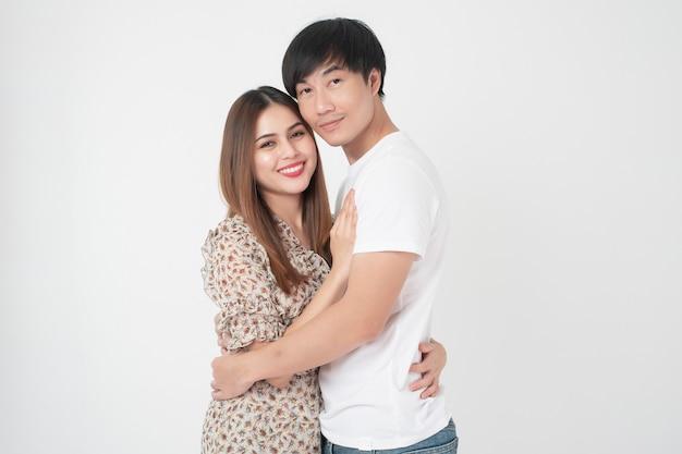 Szczęśliwa młoda azjatykcia para miłość w pracownianej biel ścianie